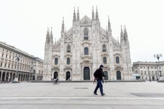 A man walks in Duomo square in Milan