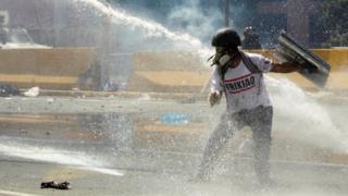 Manifestante recibe un chorro de agua de un carro hidrante.