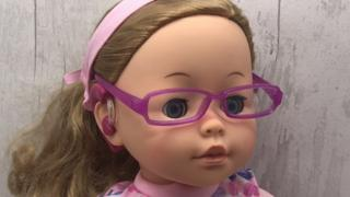 Doll with glasses and hearing aid