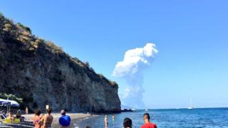 Tourists look on at an explosion in the distance