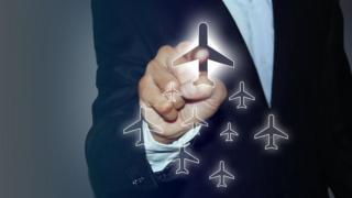 """Una persona """"haciendo clic"""" en un avión en una pantalla imaginaria"""