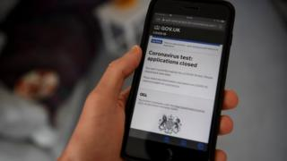 A mobile phone shows the government's coronavirus test application website