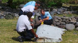 File picture shows French gendarmes and police inspecting a large piece of plane debris which was found on the beach in Saint-Andre, on the French Indian Ocean island of La Reunion, 29 July 2015
