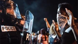 米ノースカロライナ州シャーロットで男性が警官に射殺されたことに抗議する人たちと、制止する警官隊