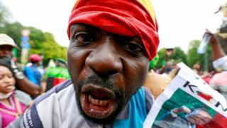in_pictures A man with the Cameroonian flag wrapped around his head looks down the camera lens.