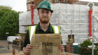 Apprentice Kane with newspaper