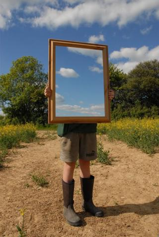 A person stands in a field and holds a mirror showing the sky