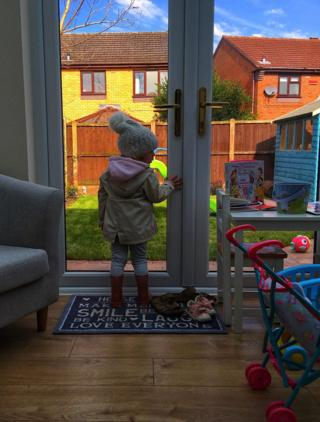 Child at a glass door
