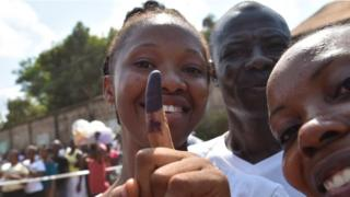 A women shows her finger after voting for the general elections, on March 7, 2018 at a polling station in Freetown. More than 3.1 million voters are registered for the polls across the small West African nation
