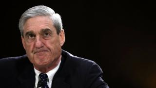 Robert Mueller in suit and tie against a black backdrop