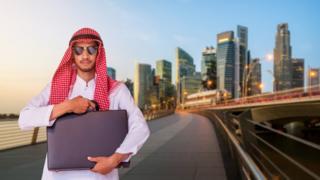 Trabajador árabe con maletín en una calle.