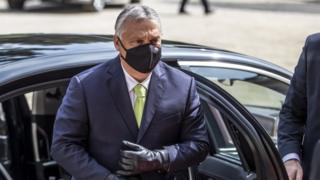 Viktor Orban in a face mask exiting a car