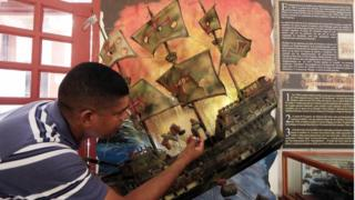A picture made available on 07 December 2015 shows a man with an illustration of the Spanish galleon San Jose during a press conference to announce the finding of the shipwreck in the Colombian Caribbean, in Cartagena, Colombia, 05 December 2015