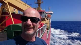 Peter Gibbs in foreground onboard the ship. Bright blue sky and deep blue ocean is behind him.
