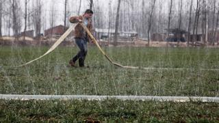 This photo taken on 8 February 2011 shows a Chinese farmer watering his drought-stricken wheat field in Luoyang, north China's Henan province, as the worst drought in six decades affecting large swathes of northern China.