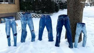 กางเกงยีนส์ตั้งอยู่บนหิมะกลางแจ้ง
