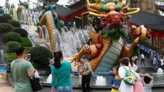 "Visitors take photos beside a dragon fountain at an outdoor theme park of the newly-opened Wanda Cultural Tourism City or ""Wanda City"" in the eastern city of Nanchang in Jiangxi Province, China, 28 May 2016"