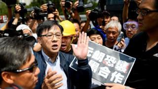 何君尧(中)参观香港警察机动部队行动基地后被泛民主派议员包围(12/8/2019)