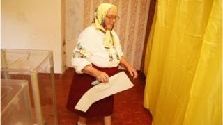 Літня жінка заходить в кабіну для голосування