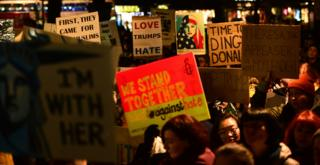 """Demonstrators hold placards as they march from the Mound to the Scottish Parliament to protest against President Trump""""s Muslim travel ban to the USA on January 30, 2017 in Edinburgh"""