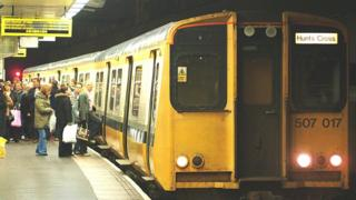 passengers board Merseyrail train