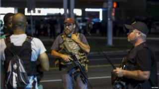 Members of the Oath Keepers walk with their personal weapons on the street during protests in Ferguson, Missouri 11 August 2015
