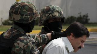 "In this 22 February file photo Joaquin ""El Chapo"" Guzman is escorted to a helicopter by Mexican navy marines"