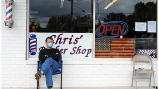 a man in a mask sits in front of his barber shop