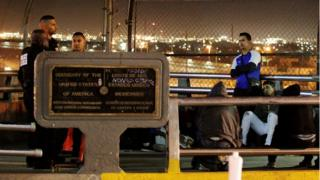 A group of Central Americans and Cubans hoping to apply for asylum wait at the border on an international bridge between Mexico and the US