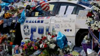 Notes, flowers and other items decorate a police car at a make-shift memorial in front of the Dallas police department on 9 July