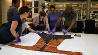 Collections officer Abigael Flack shows volunteers a textile from Syria