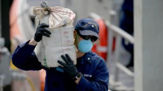 A US Coast Guard officer carries a bundle of seized cocaine