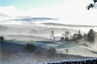 Misty and frosty sunrise over landscape