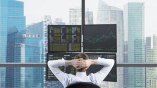 Inversor mirando sus acciones desde su oficina en un rascacielos