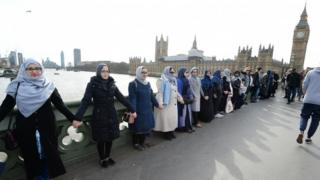 A group of women, some with their daughters, link hands on Westminster bridge