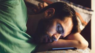 man asleep by phone