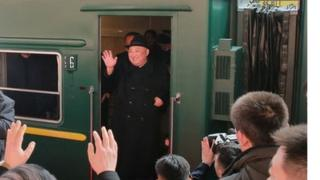 North Korean leader Kim Jong Un waves from a train in Beijing