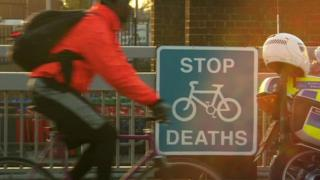 Man cycling past sign saying: Stop cycle deaths