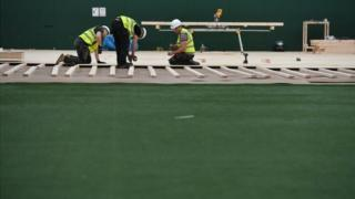 Workers lay flooring during the construction of a field hospital at Llandarcy sports academy in Neath