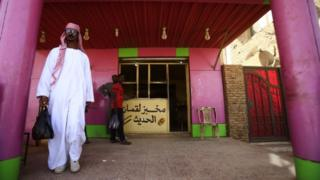 A Sudanese man leaves a bakery with a bag of bread in the capital Khartoum on January 5, 2018. Angry Sudanese queued outside bakeries in Khartoum as bread prices doubled overnight, with bakers blaming a government decision to stop importing wheat. Men, women and children had to wait for nearly an hour to to buy bread, while several bakery operators said price hikes on flour meant they would be forced to stop production entirely.