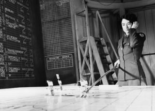 Corporal Geraldine Hill of the Women's Army Corps, receives reports on aircraft positions in the plotting room of the 3rd Bomb Division at Elveden Hall, Suffolk