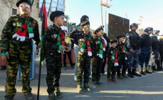 Libyans children dressed in military fatigue stand at attention during a gathering to commemorate the ninth anniversary of the uprising against former Libyan leader Muammar Gaddafi in the capital Tripoli on 17 February 2020.
