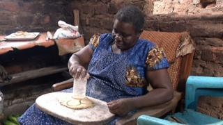 Joyce Namugalu Mutasiga pressing out pancakes from pastry