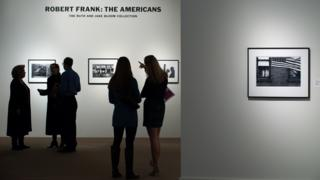 "People look at rare Robert Frank photographs from his book ""The Americans"" at Sotheby's on 17 December 2015 in New York City."