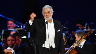 Placido Domingo singing on stage with an orchestra behind him
