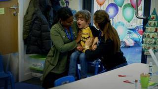 Dos miembros de la escuela especializada ayudando a Cruz.