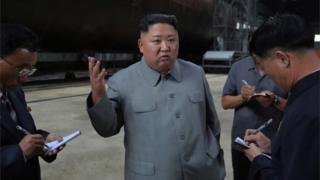 Picha iliotolewa na chombo cha habari cha Korea Ksakzini (KCNA) tarehe 23 Julai 2019 inamuonyesha Kim Jong-Un (kushoto), akizungumza na maafisa baada ya kuikagua manowari mpya katika eneo lisilojulikana Korea Kaskazini
