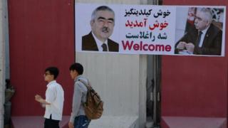 Afghan residents walk past a banner with the image of self-exiled Afghan Vice President Abdul Rashid Dostum