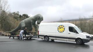 A team loading the dinosaur on to the trailer