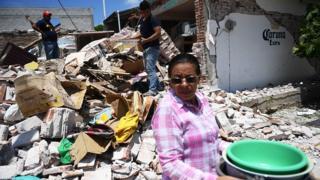 Una mujer retira pertenencias entre los escombros en Oaxaca, México, tras el terremoto del jueves.